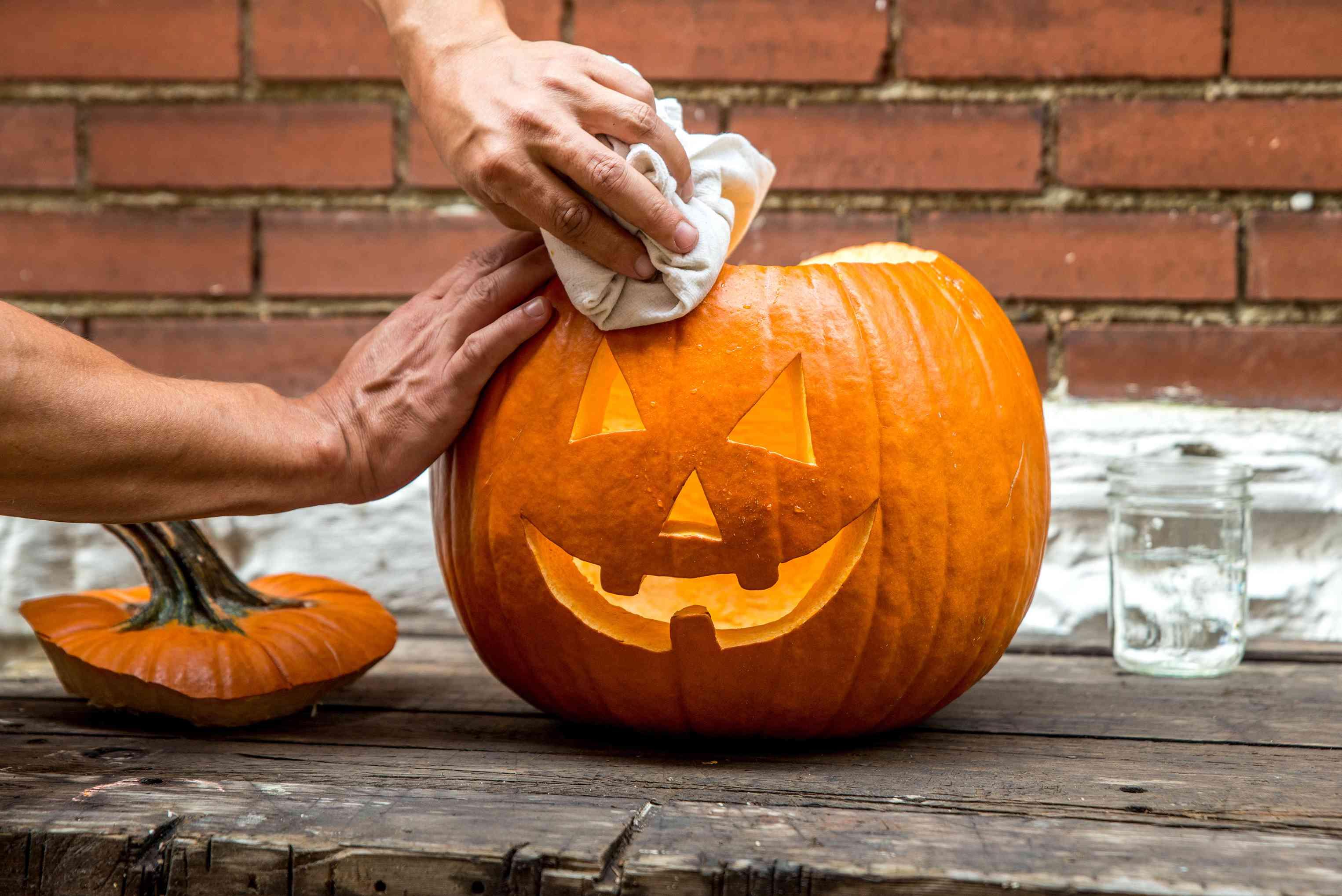 hands wipe off carved pumpkin outside