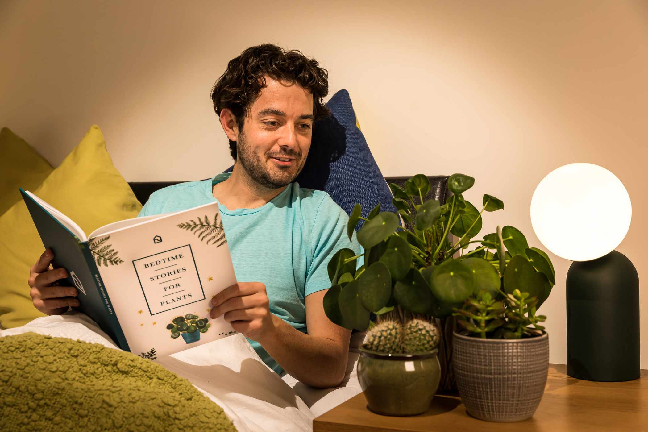 a guy in bed reads a book to his three plants