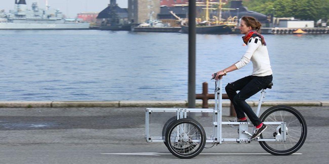 Woman riding a cargo bike along a waterfront street