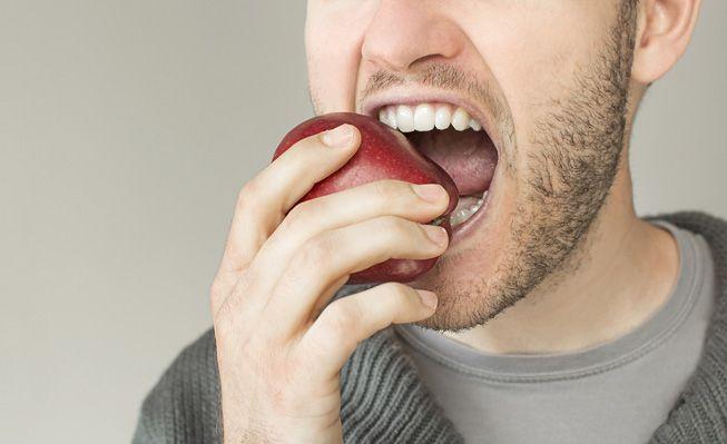 A bearded man bites into an apple