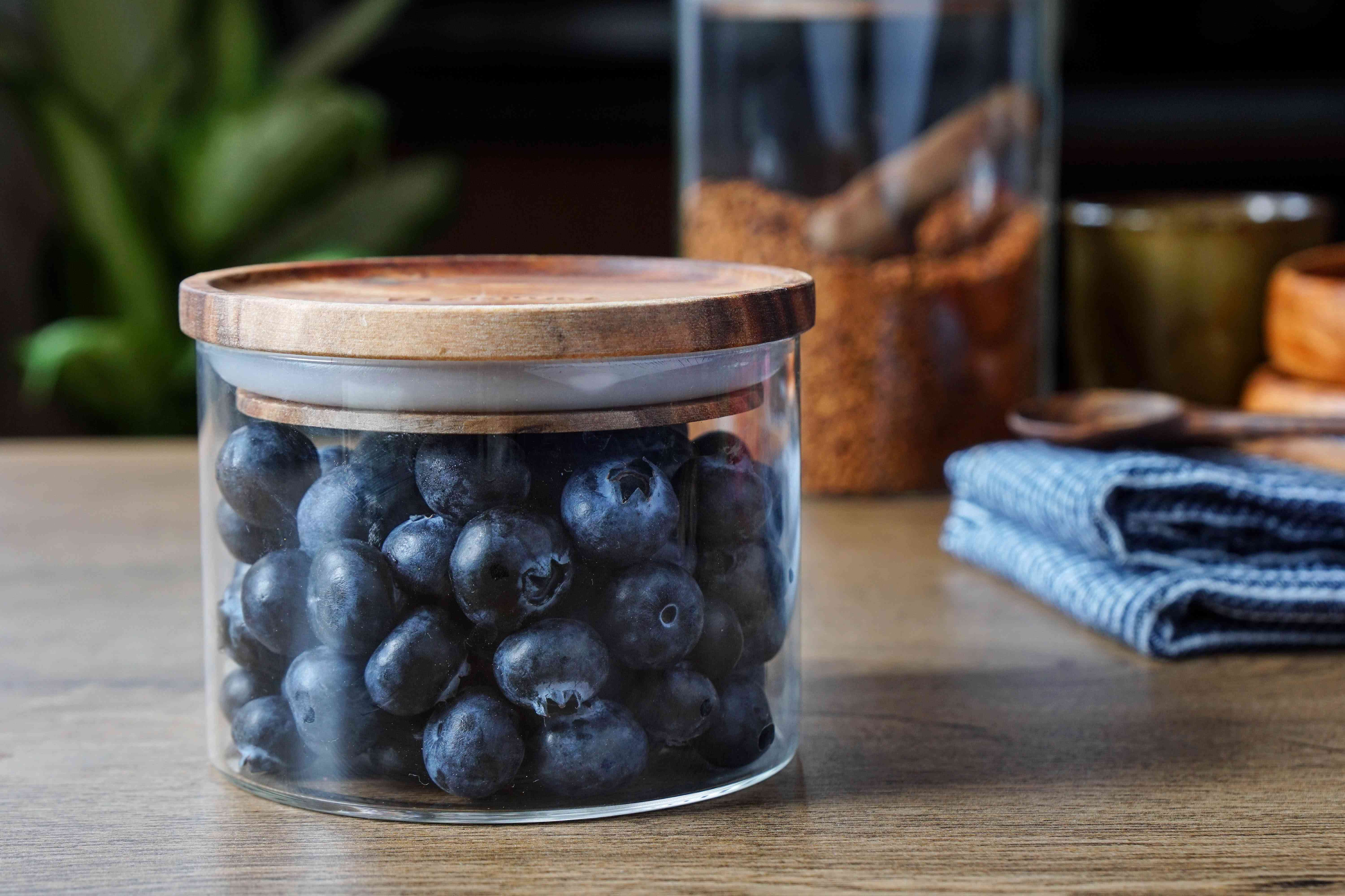 glass storage container filled with blueberries and topped with a wooden rubber-lipped lid