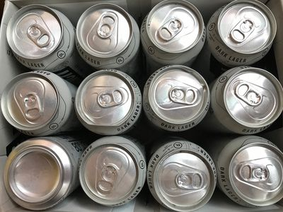 Birds-eye view of the tops of a dozen silver beer cans