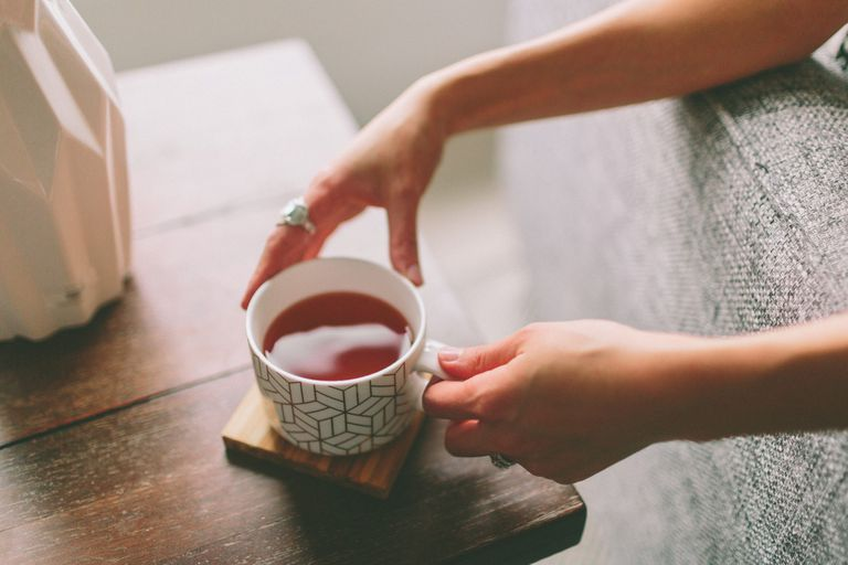 A woman's hands holding a cup of tea.