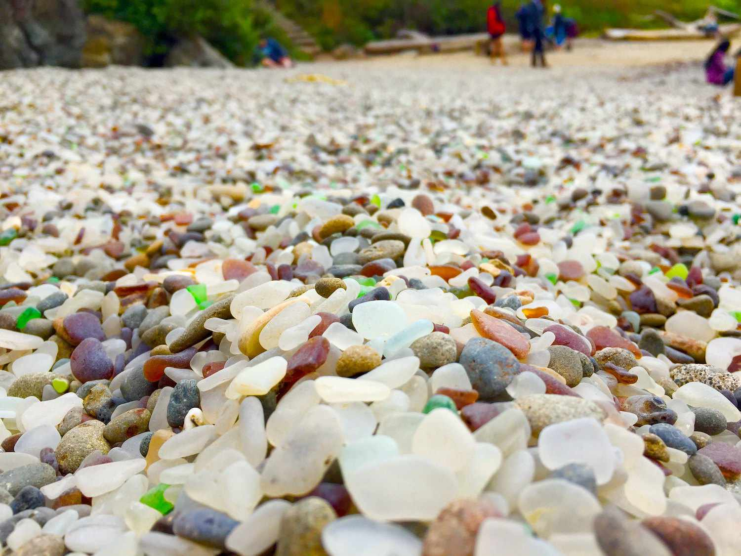A closeup of small, smooth rocks and glass on Glass Beach in California