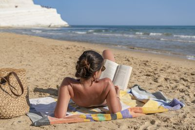 A woman sits on a towel reading a book tanning on a beach.