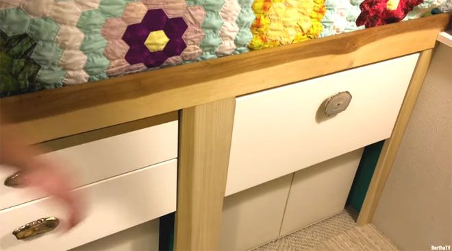 White drawers beneath bed