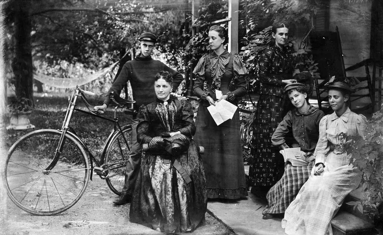5 women and a man with a bicycle posing on front porch in 1890