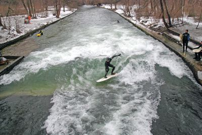 Surfer in the middle of the Eisbach surfing in winter with snow on both sides of the river and a forest of trees with brown leaves