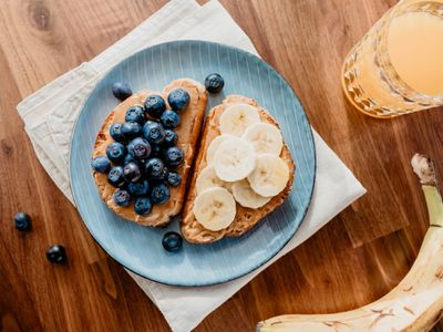 Two pieces of toast, one with peanut butter and banana and one with peanut butter and blueberries