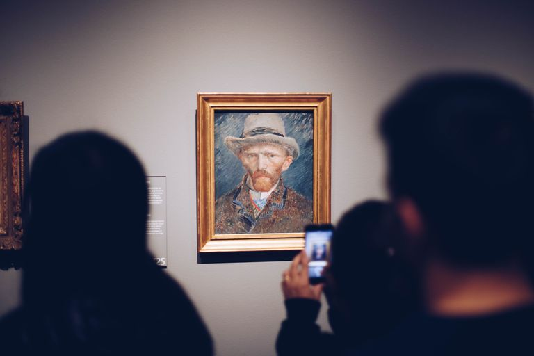 People taking photos of a self-portrait of Van Gogh on the wall of a museum