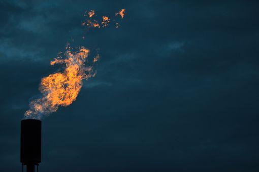 A Methane Flare Burns Against A Twilight Sky
