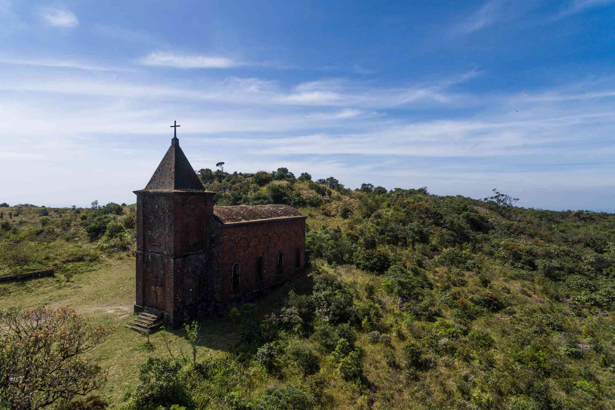 Aerial view of Bokor Hill Station, an abandoned church surrounded by lush green trees and plants on top of a hill inside of Preah Monivong National Park under a blue sky with light clouds