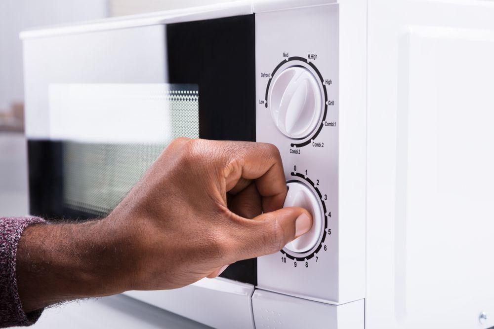 woman's hand turning microwave knob