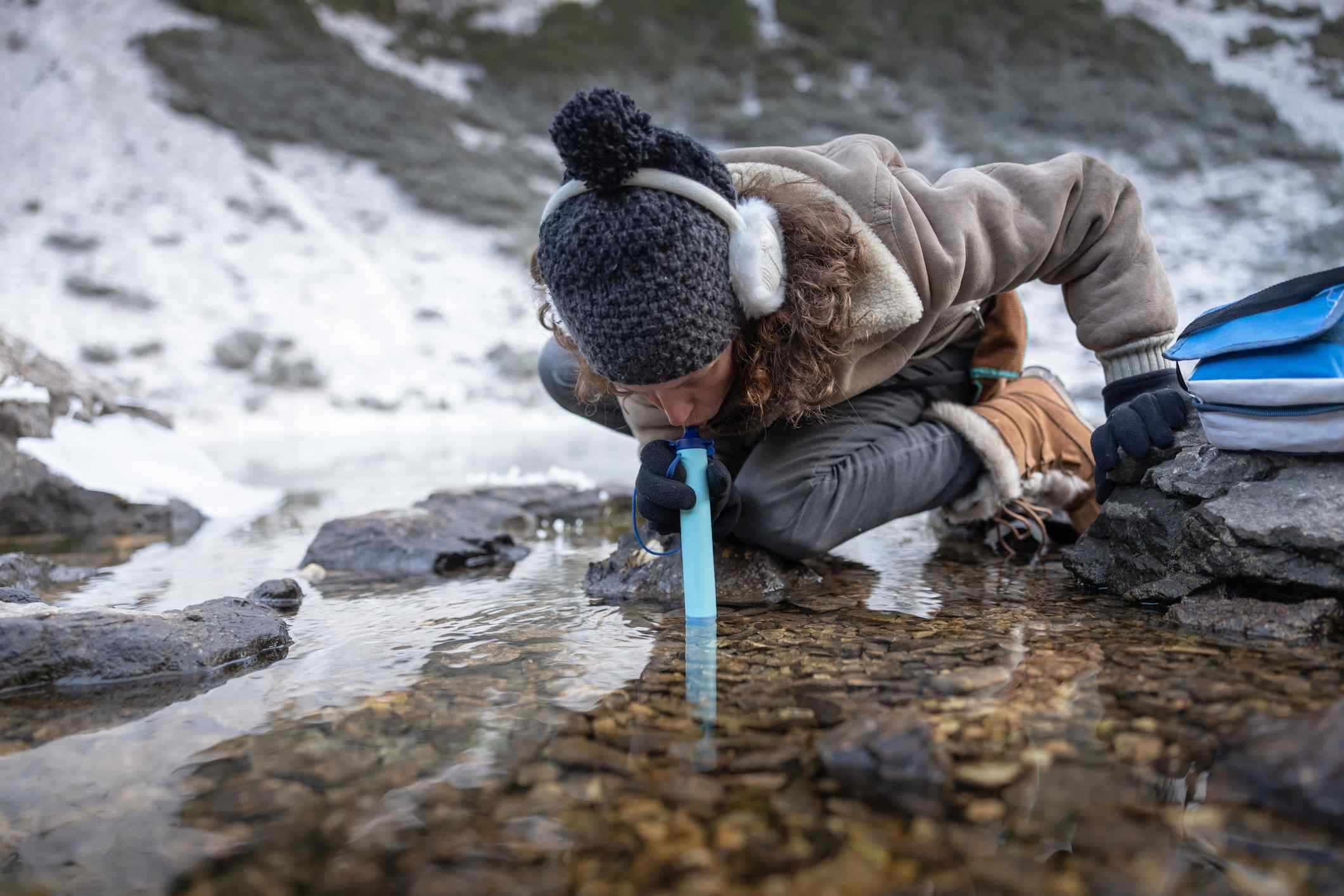 woman using a water filtration straw outside in a stream, winter