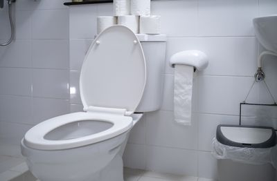 A toilet in a white sterile bathroom.