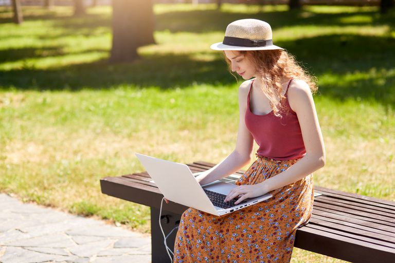 Woman sitting on park bench using her laptop with a solar charger next to her