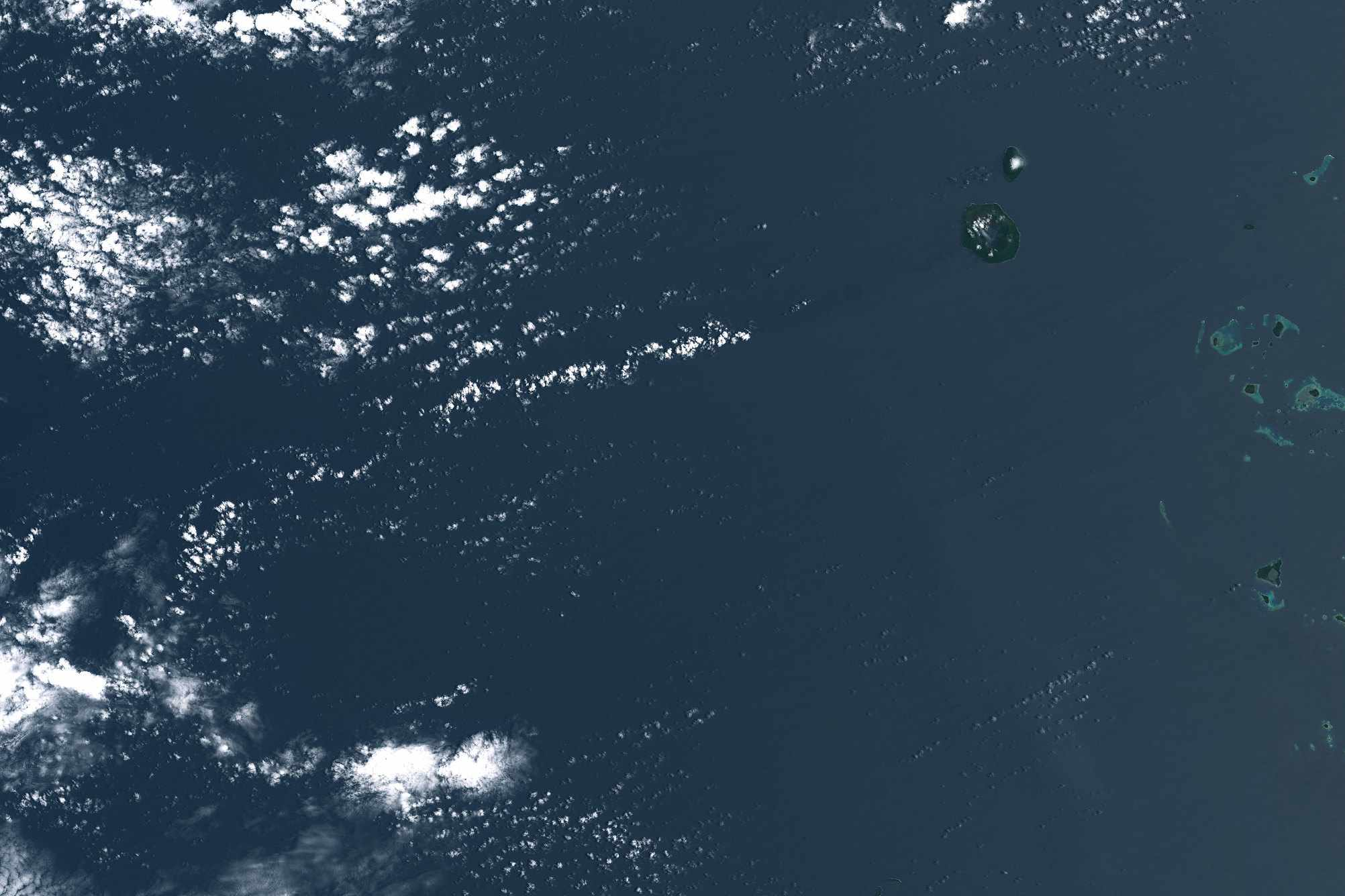 Satellite imagery of new island surrounded by sea and clouds