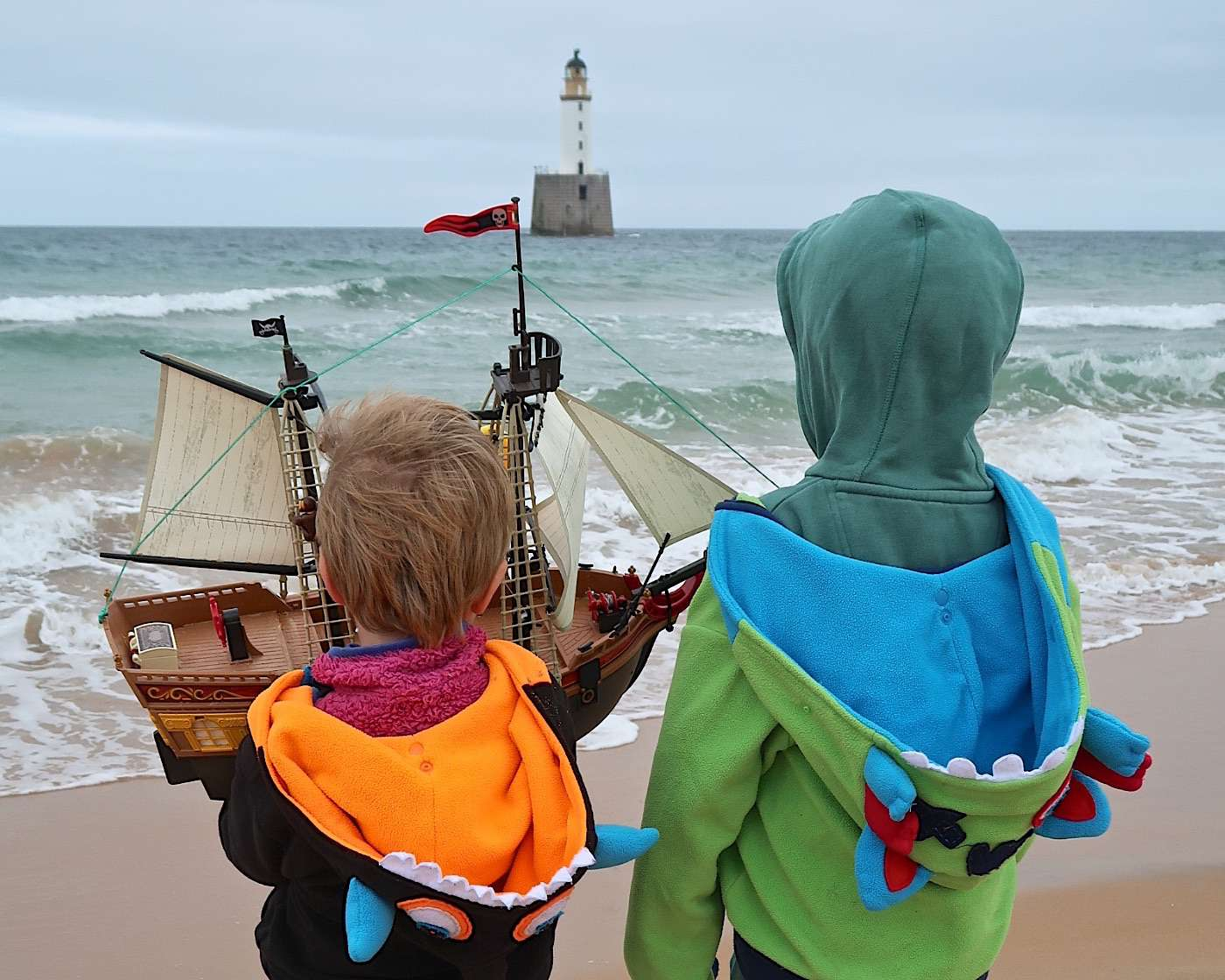 Harry and Ollie hold the Adventure as they look out to sea.