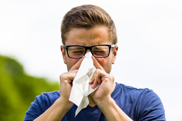 Person sneezing into a tissue