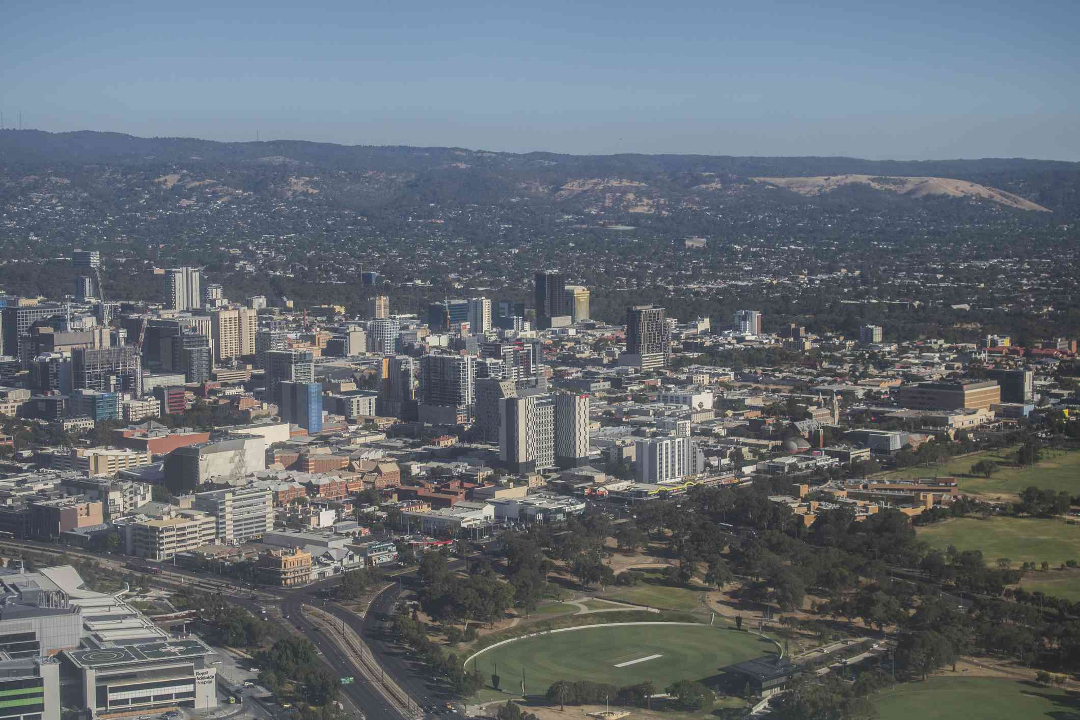 Aerial view of Adelaide central business district's tall office buildings surrounded by public green space lined with lush trees with green hills in the background under a hazy blue sky