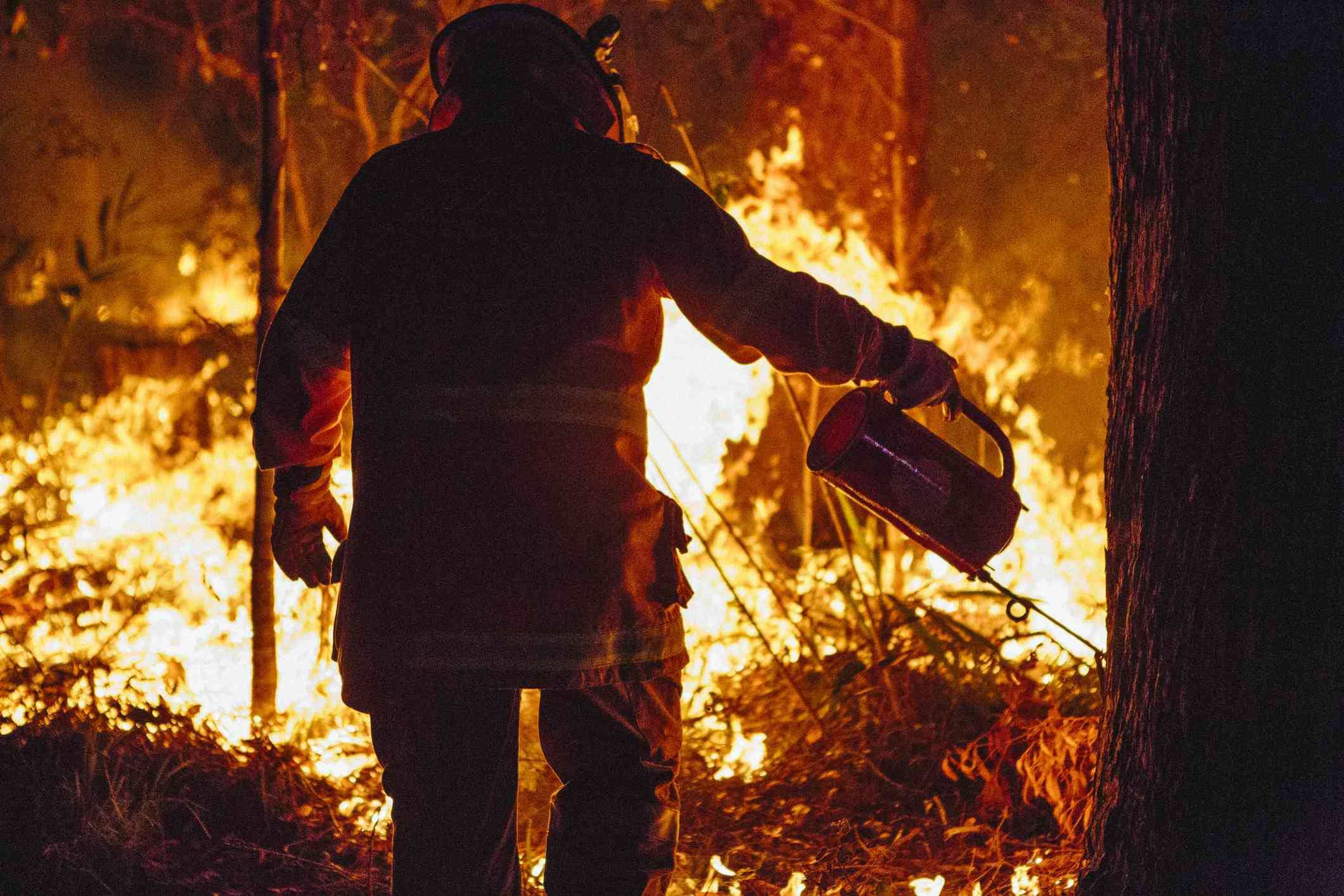 A firefighter conducting a controlled burn with a drip torch