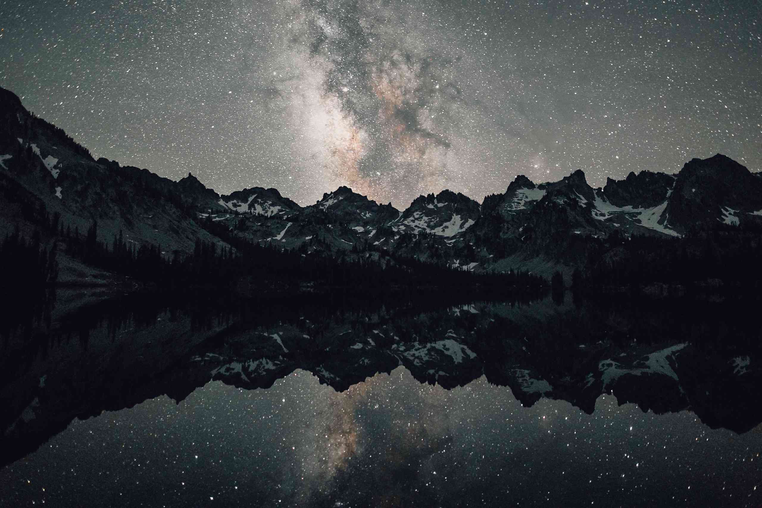 Milky Way over snowy mountains reflecting on lake