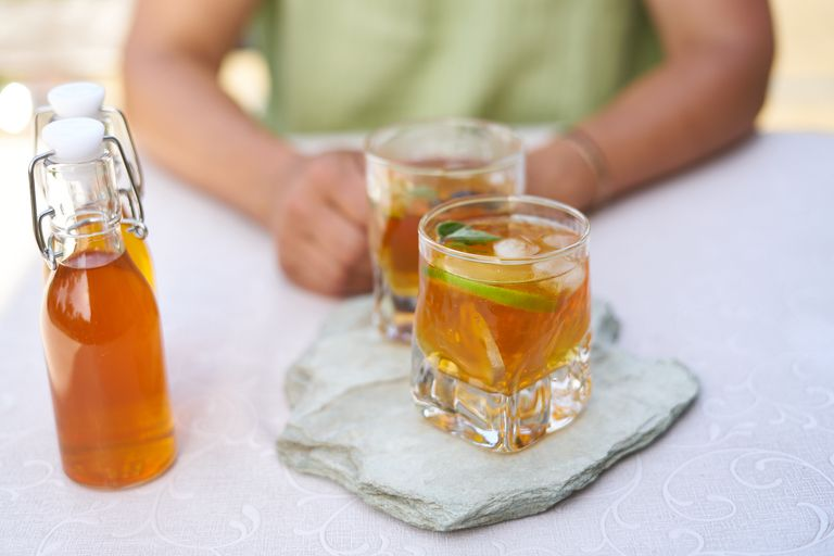 two glasses filled with DIY kombucha on stone plate across from person in green shirt