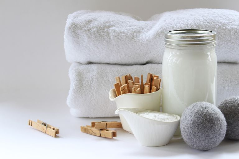 sustainable laundry detergents in glass containers with towels and clothespins