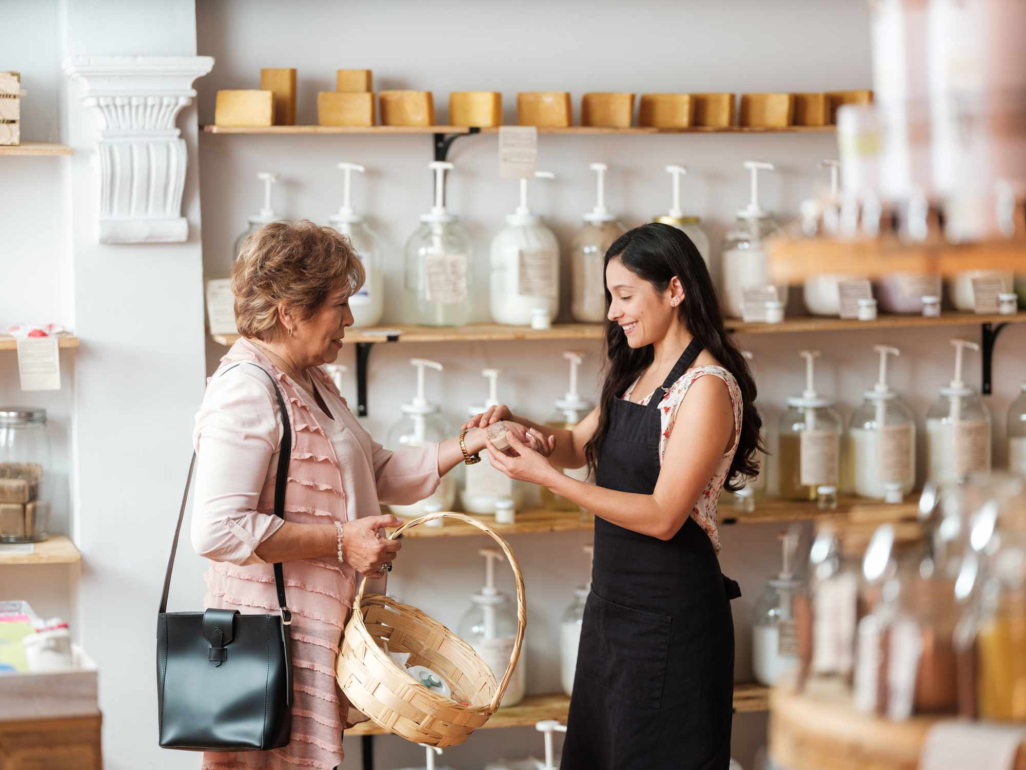 A senior Latino woman being helped by a younger woman at a sustainable shop.