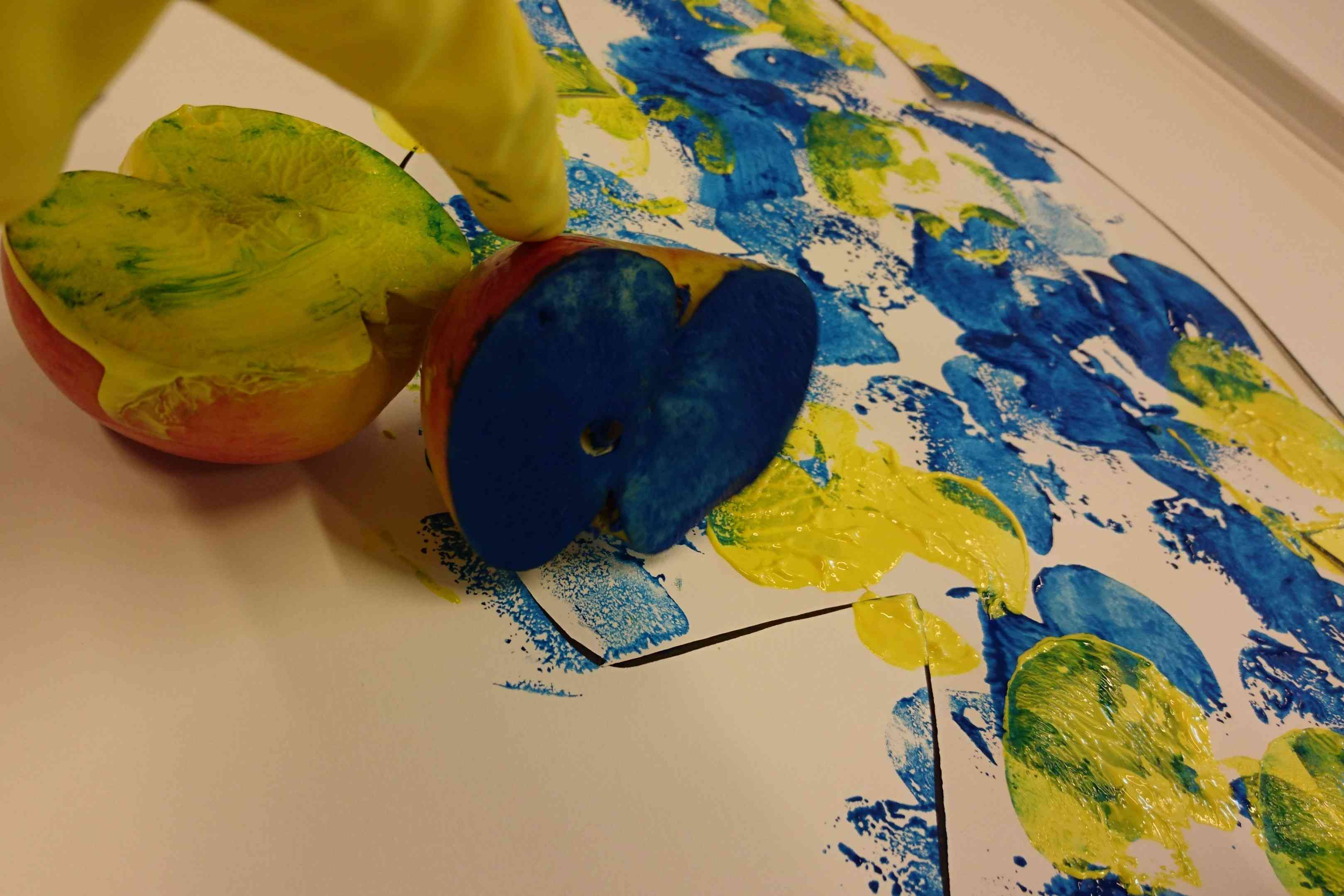 A halved apple covered in blue and yellow paint being used to stamp paper