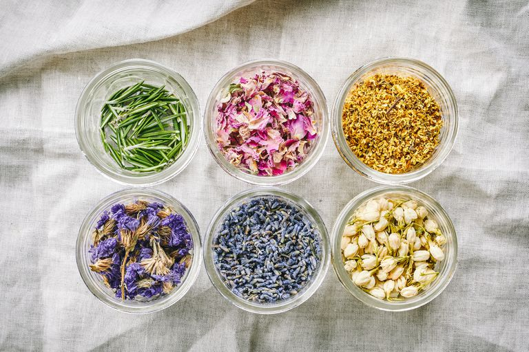 six clear glass jars filled with dried flowers and herbs on rumpled linen cloth