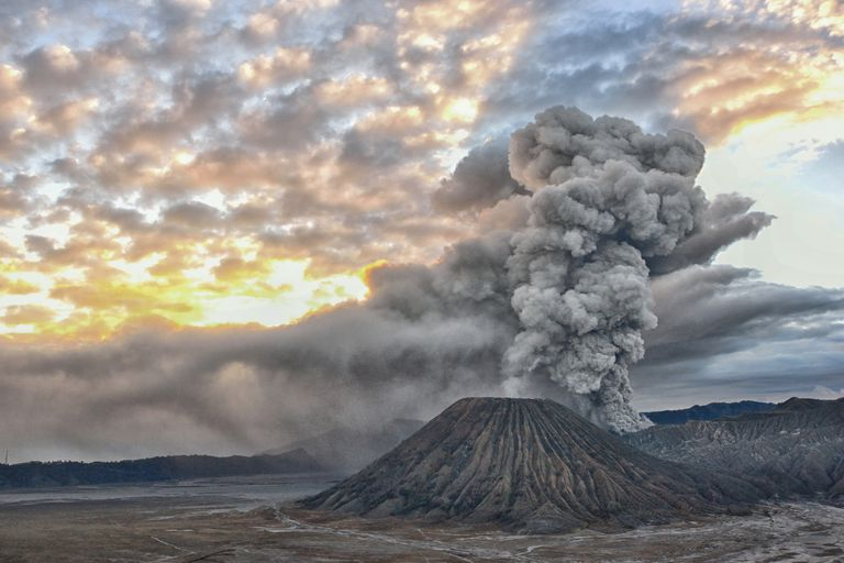 An ash cloud rises from a volcano at sunrise