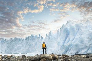 A glacier towers above a hiker at sunset.