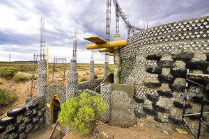 Earthship house featuring a wall build from dirt, tires, and bottles