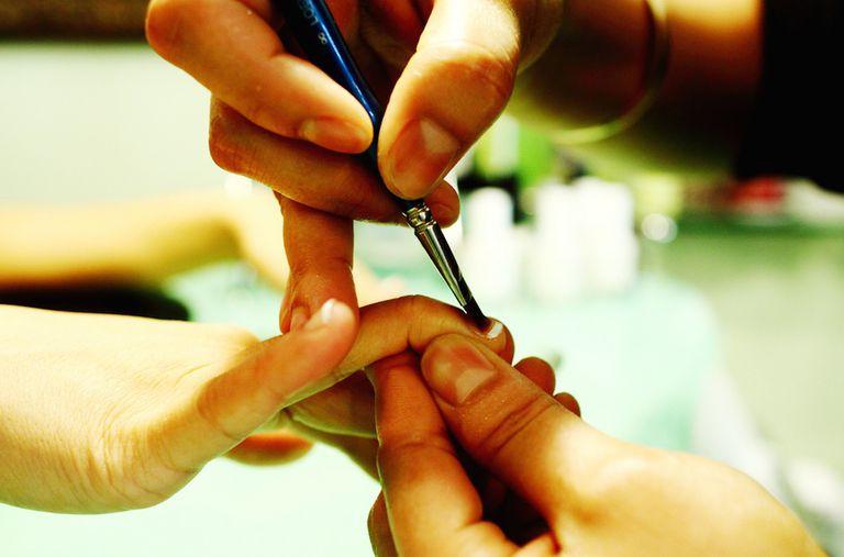 Manicurist painting fingernails