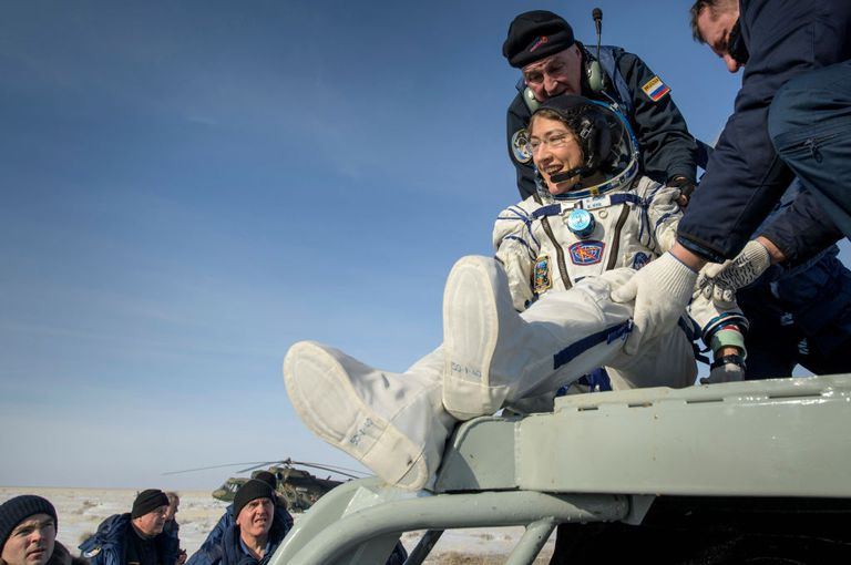 NASA astronaut Christina Koch is helped out of the Soyuz MS-13 after landing from a year in space