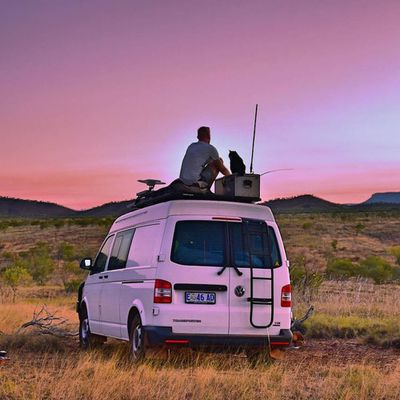 Man and cat sit atop a camper looking at a desert sunset