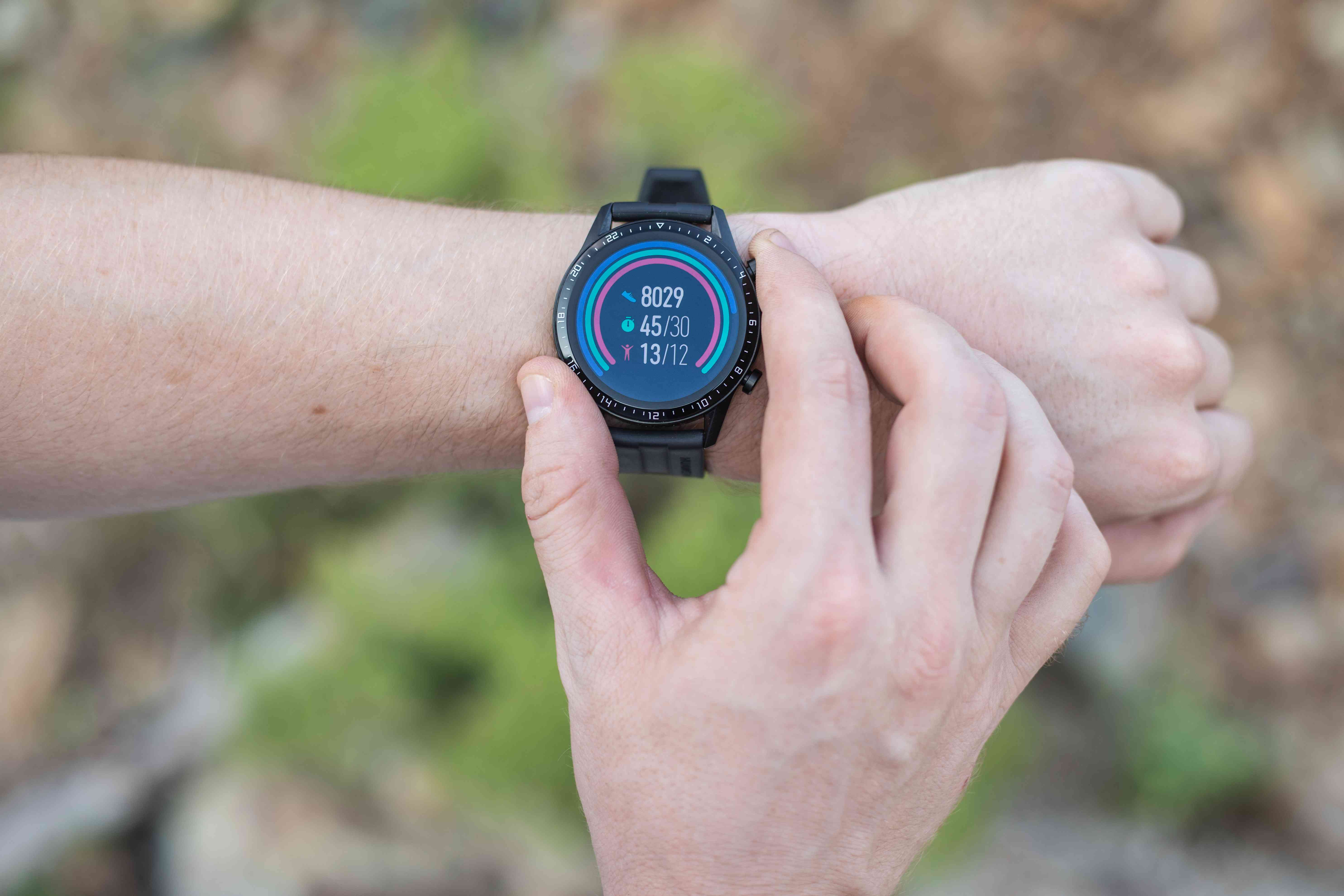 person wearing pedometer tracking watch on wrist checks their steps outside