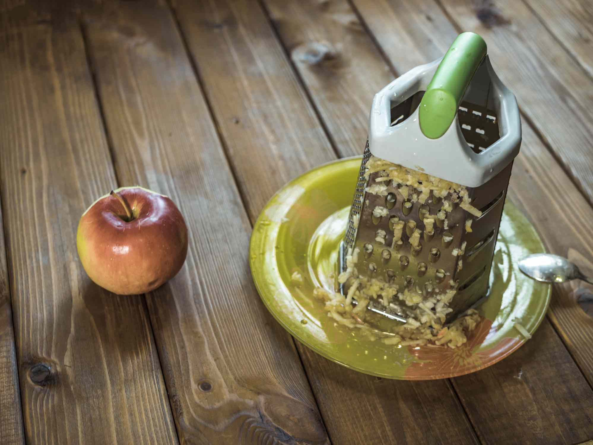 Cheese grater sitting on a plate with grated an apple