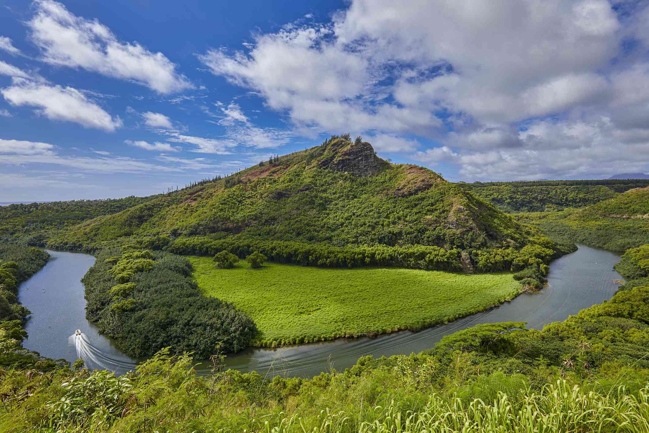 Wailua River winds around open grassy area and small mountain
