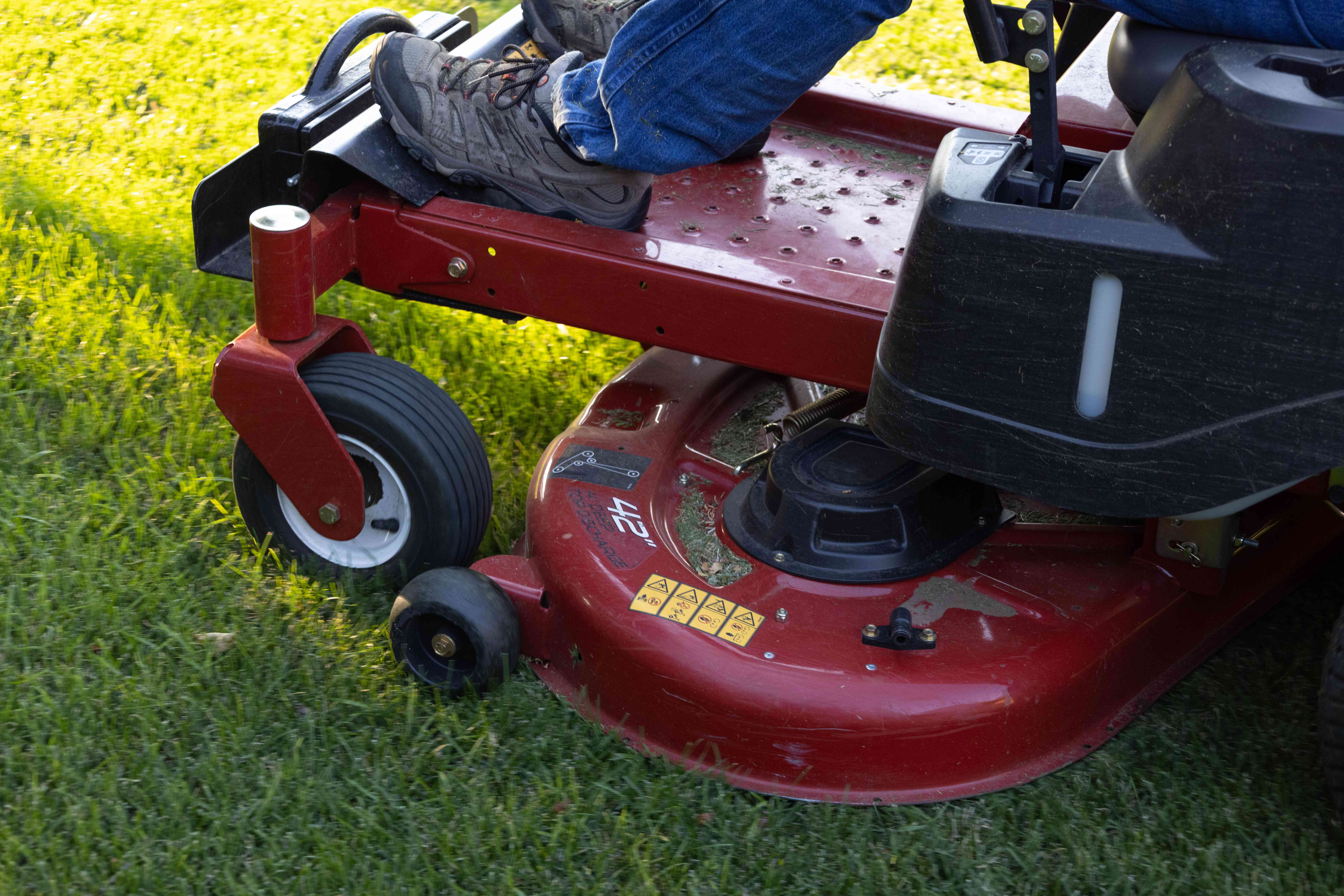 man uses red riding lawn mower to cut lawn grass closely