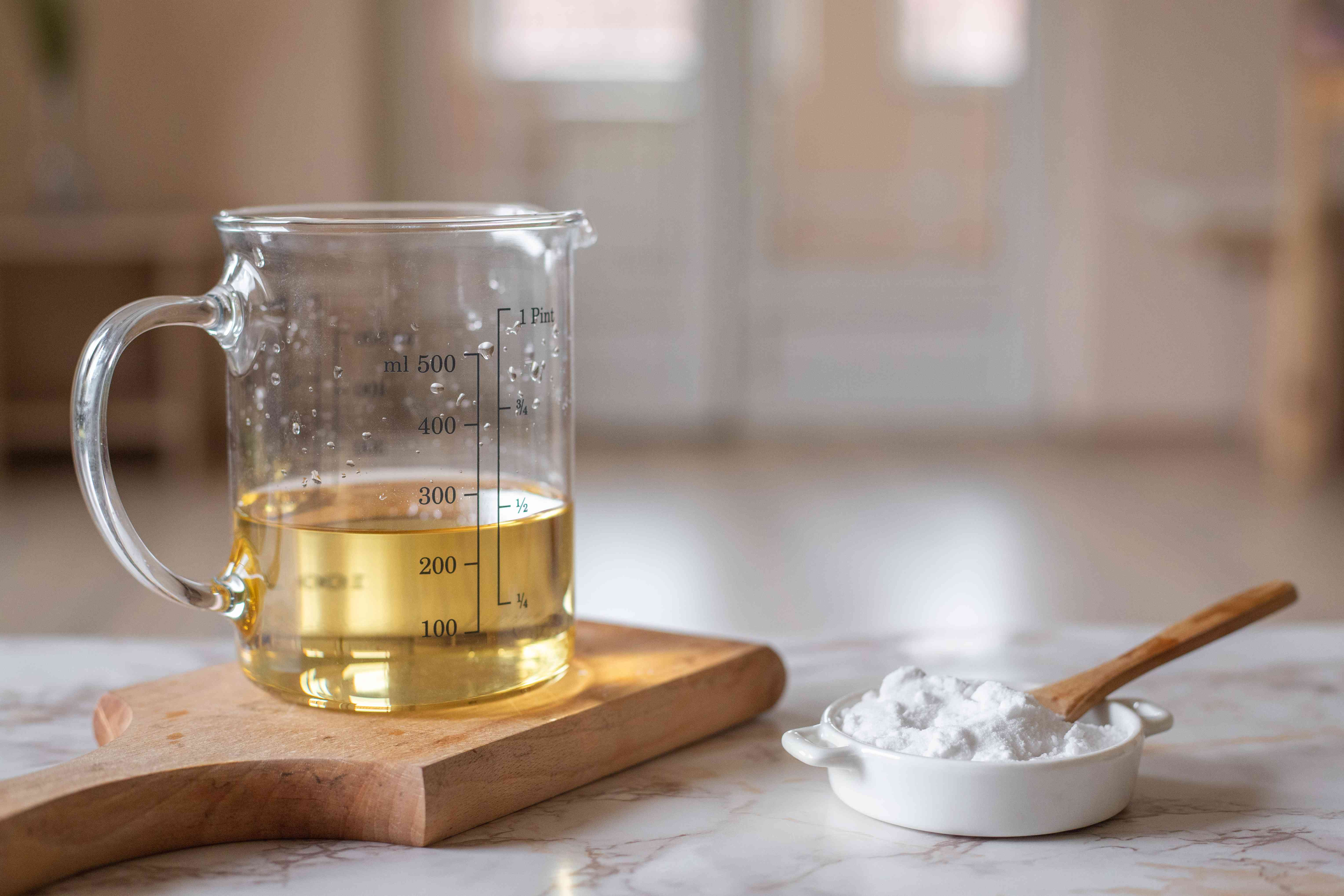 product shot of apple cider vinegar in measuring jar with baking soda in small ramekin with wooden spoon
