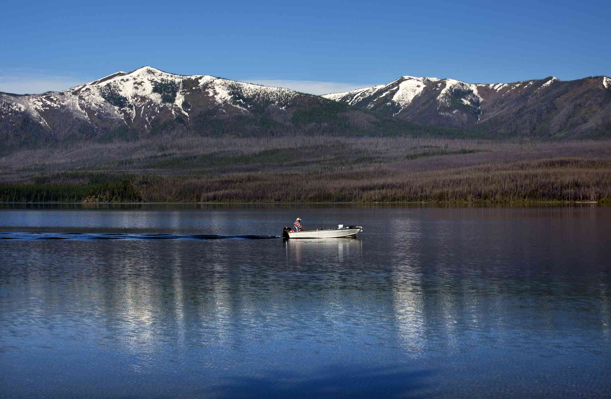 Man in a small white boat fishing on Lake MacDonald with the Snow Mountains in the distance under a clear blue sky at Glacier National Park Montana