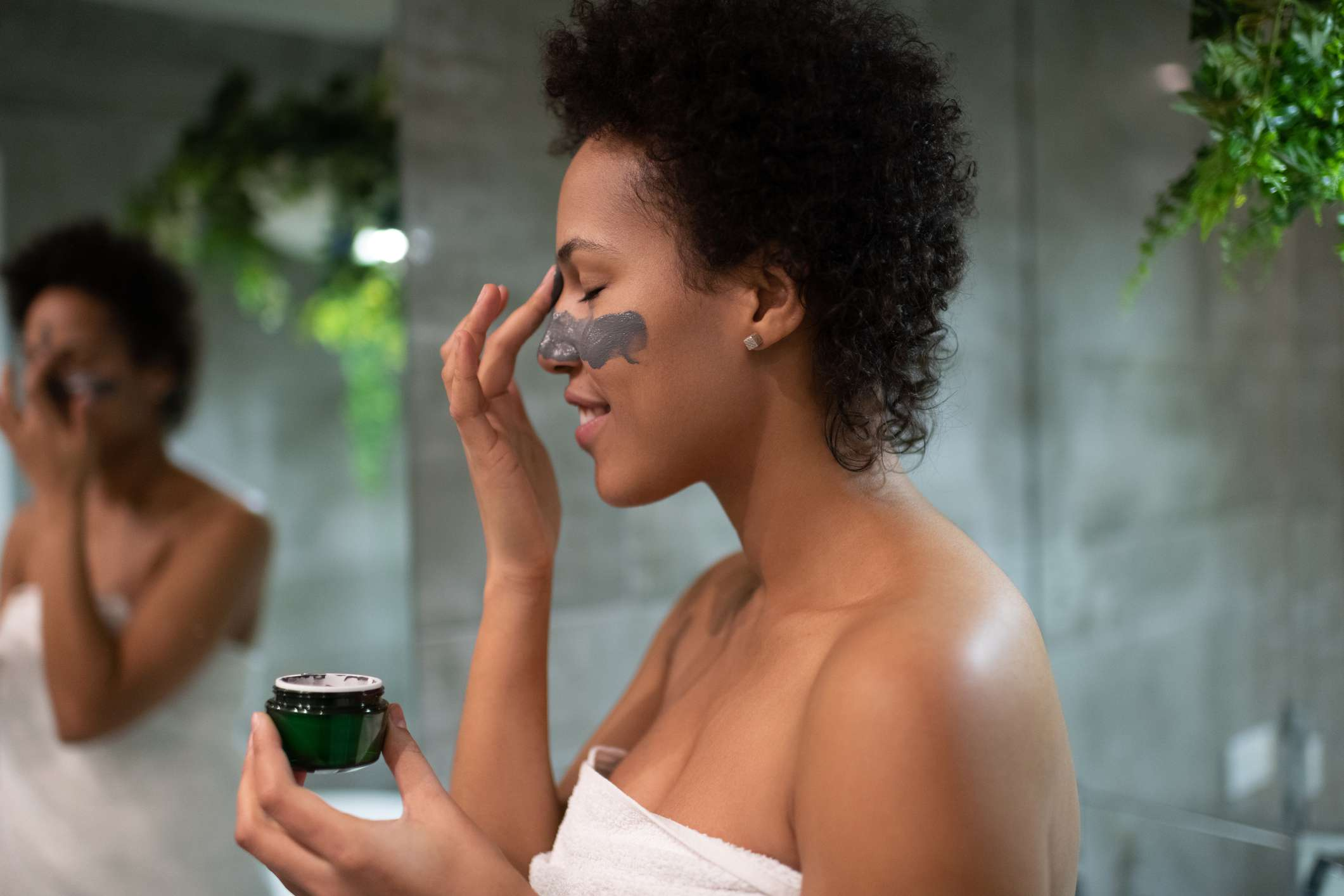 A Black woman applies clay under her eyes.