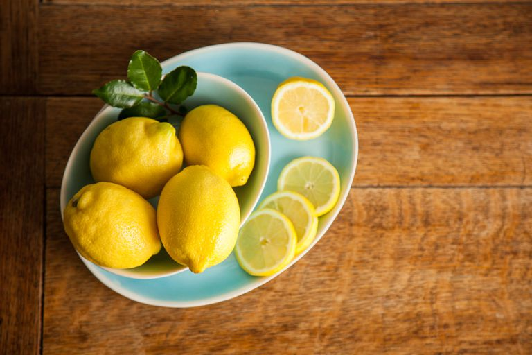 Lemons in blue bowls on a wood table.