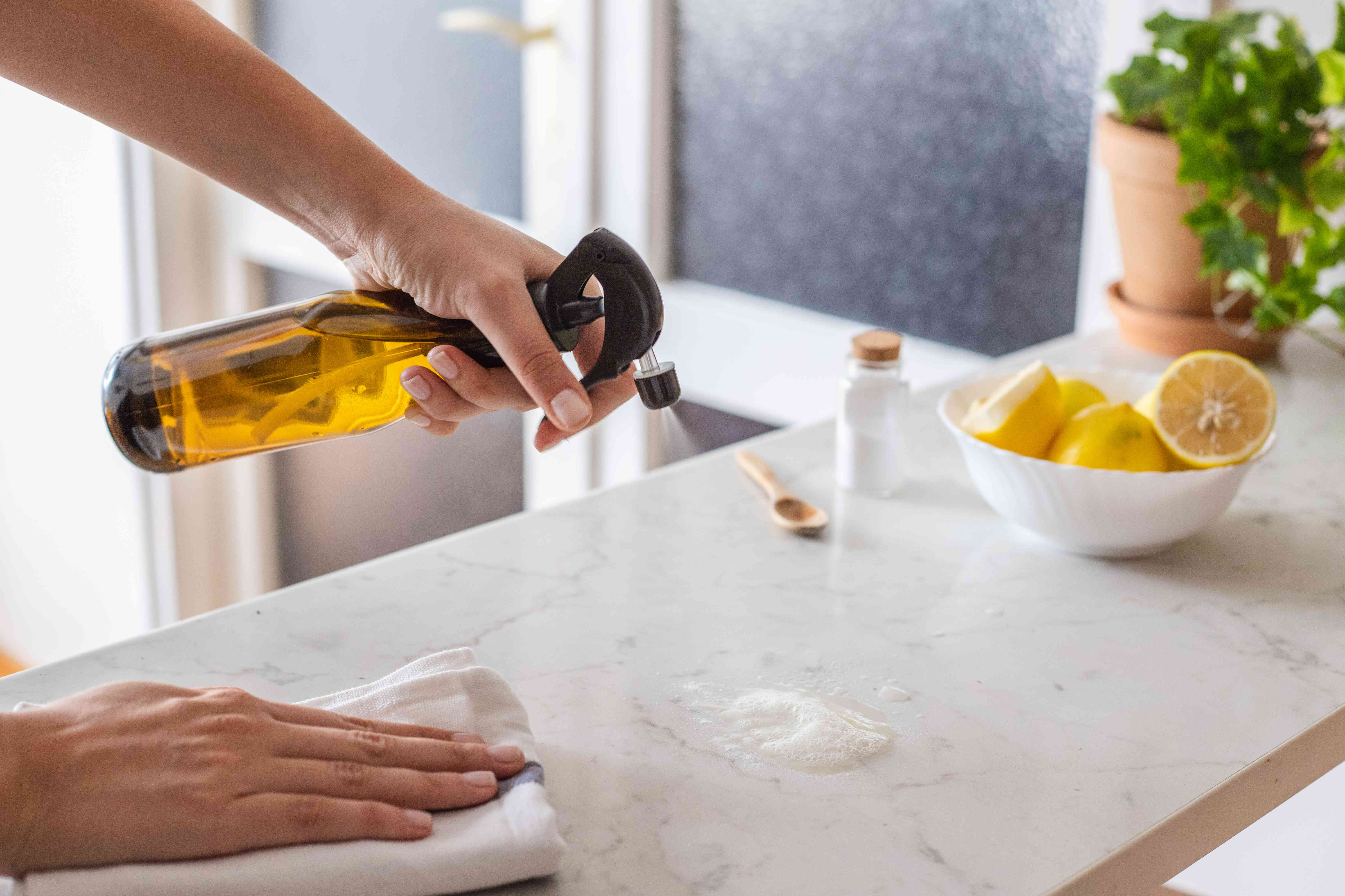 person sprays salt pile on marble countertop to clean greasy mess with lemons