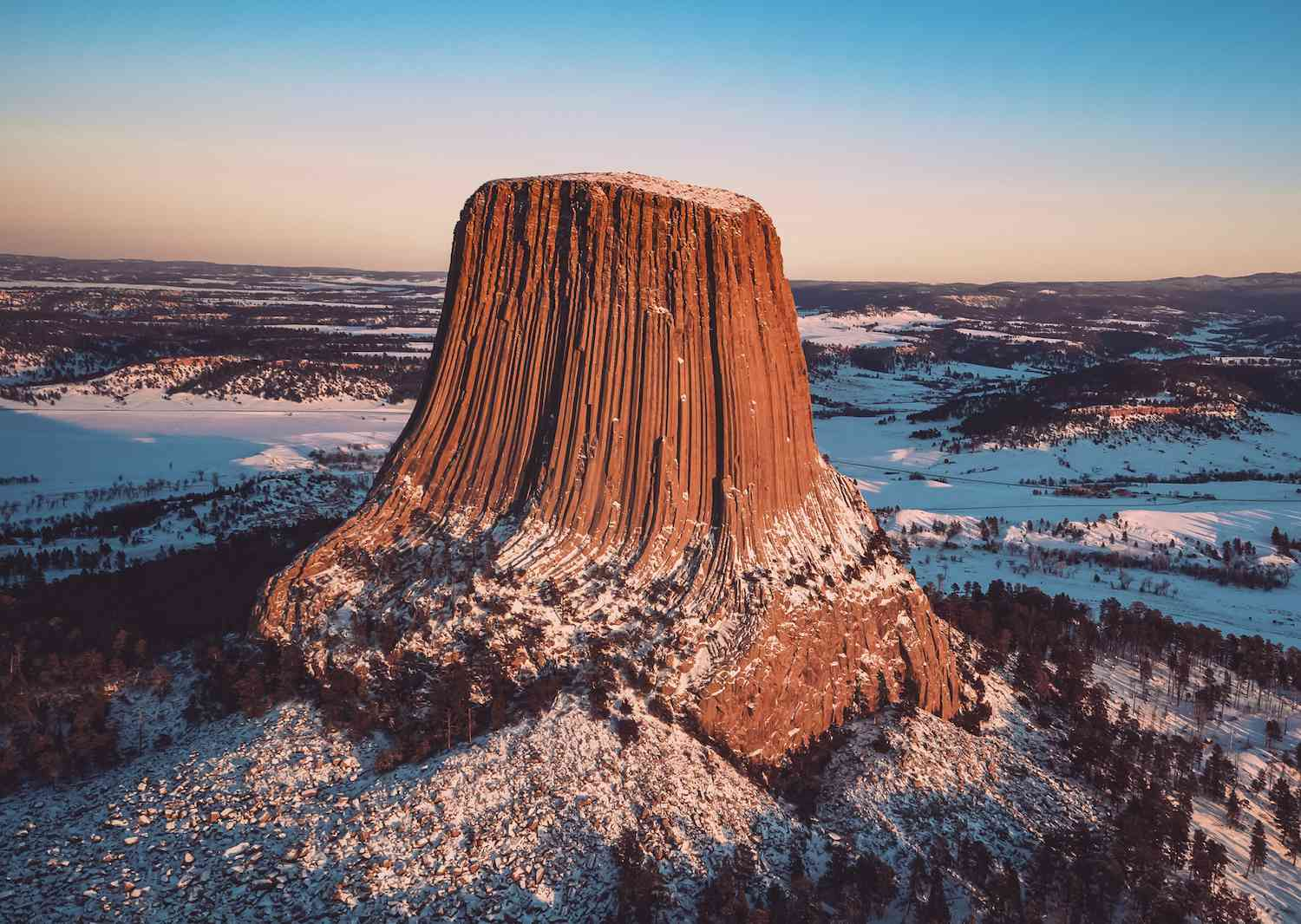 Devil's Tower rises above the snow-covered Black Hills at dawn