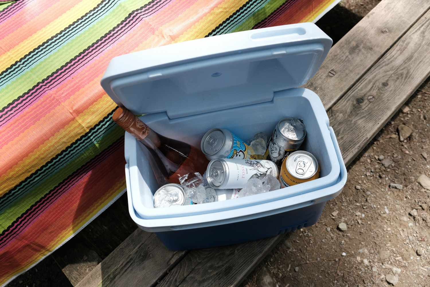 open cooler on picnic table filled with wine and beer and ice