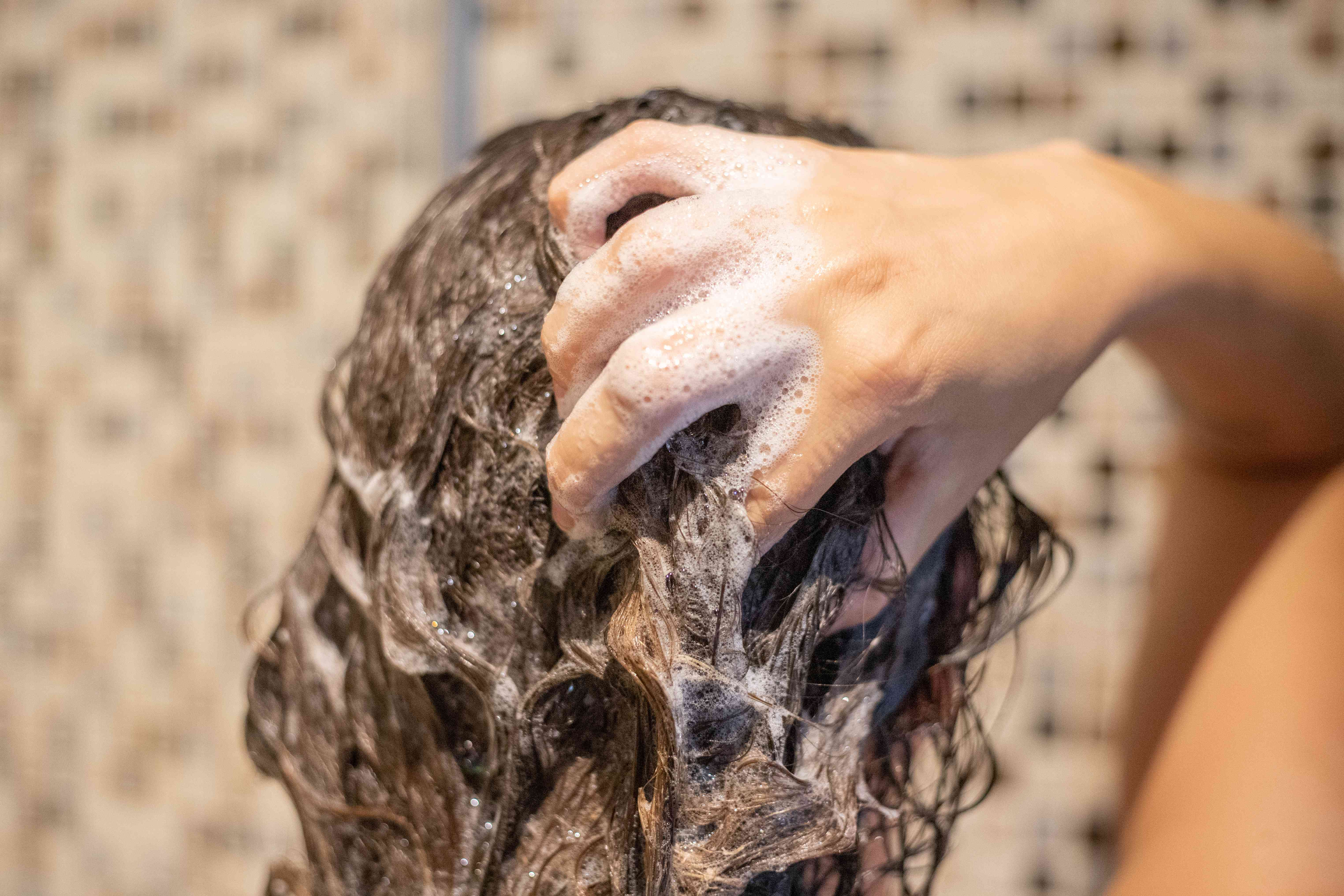 back of woman's head shampooing her hair in shower