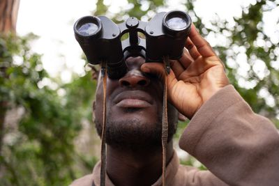 A handsome man looking at something intently through inoculars